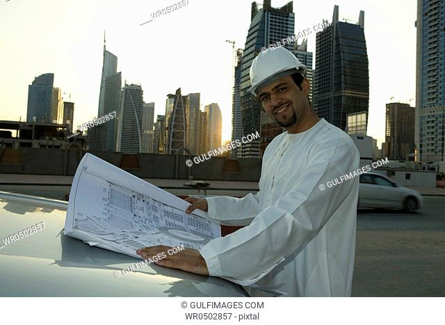 Arab man with blueprint, standing on a construction site