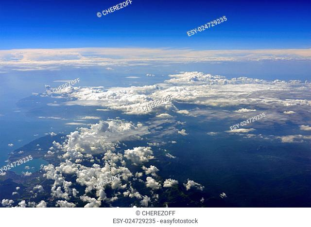 Earth's surface with sea and clouds. Top view of aircraft