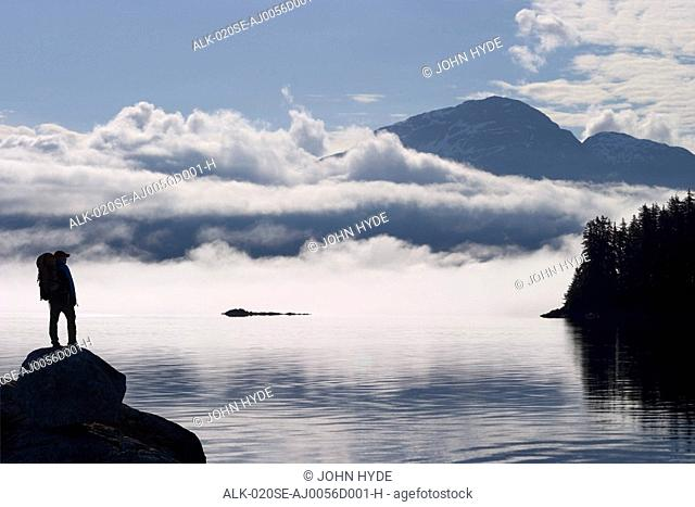 COMPOSITE: Silhouette of a backpacker along the shoreline of Lynn Canal near Juneau with Chilkat Mountains in the background, Tongass National Forest
