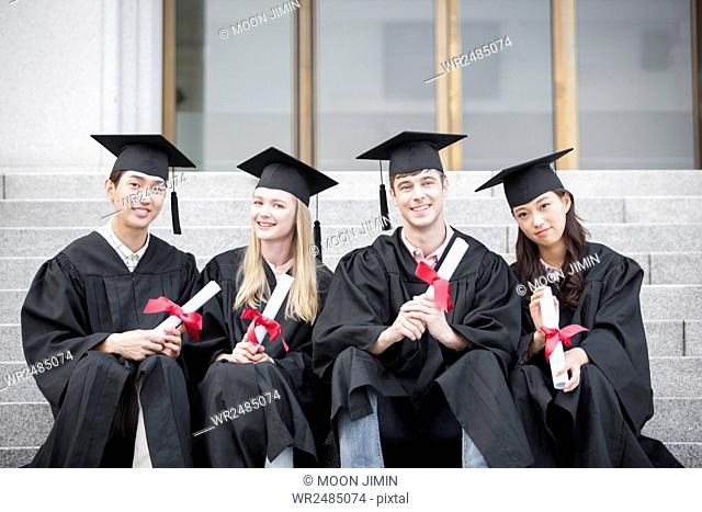 Four smiling college graduates with their certifications