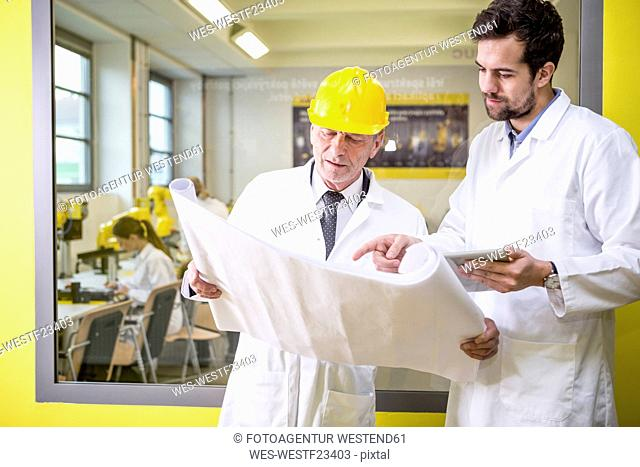 Two engineers in factory looking at plan