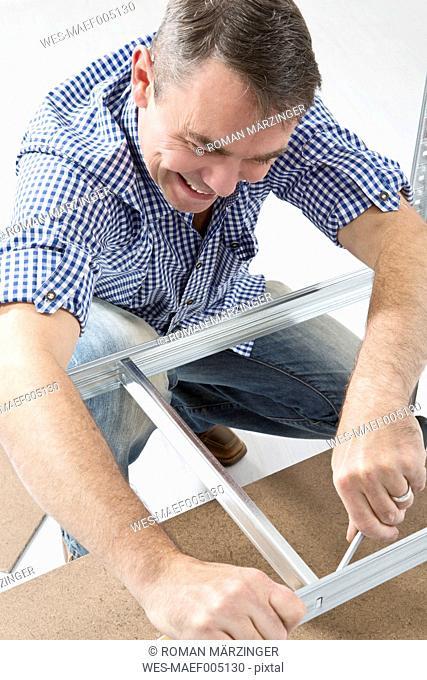 Mature man building shelf