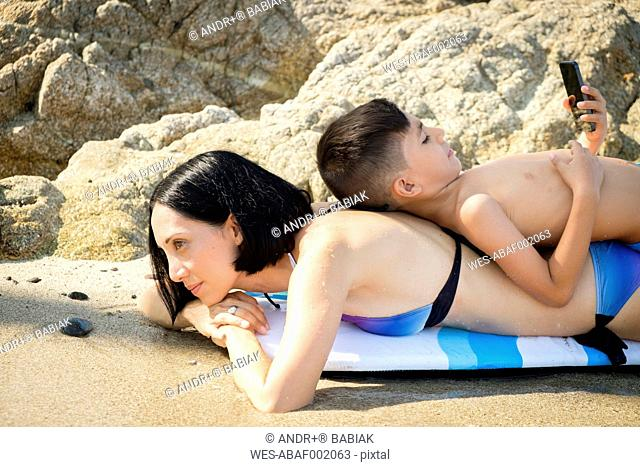 Woman resting with son lying on her back on beach