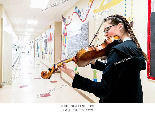 Caucasian girl playing violin in school corridor