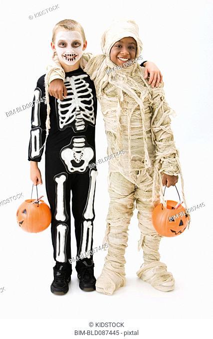 Boys in skeleton and mummy costumes holding jack o'lantern