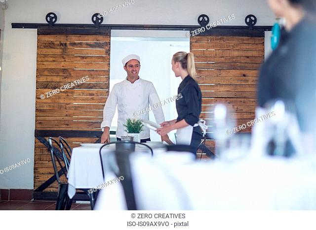 Waitress and chef chatting in restaurant