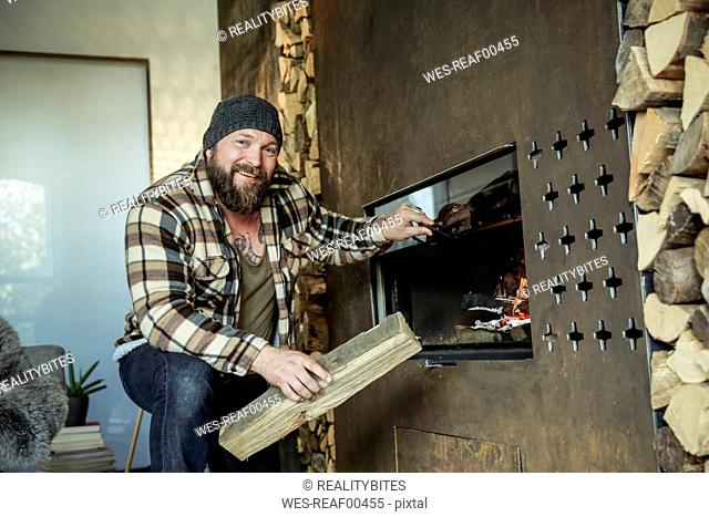Portrait of bearded man lighting fireplace at home