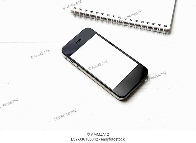 cellphone with notepad over white table