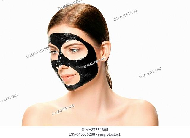 Young beautiful caucasian woman applying a black cosmetic mask for the face of the therapeutic black mud. Spa treatment and face beauty concept