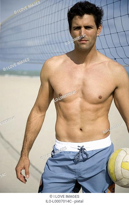 A young man playing beach volleyball