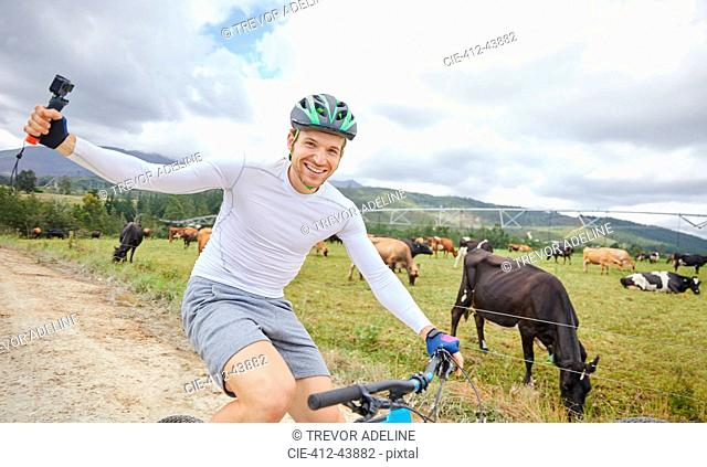 Portrait carefree man with wearable camera mountain biking on dirt road along cow pasture