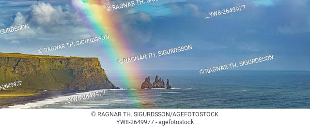 Rainbow over Mt Reynisfjall and large lava sea stacks located by the black sands of Reynisfjara beach and Dyrholaey, Iceland