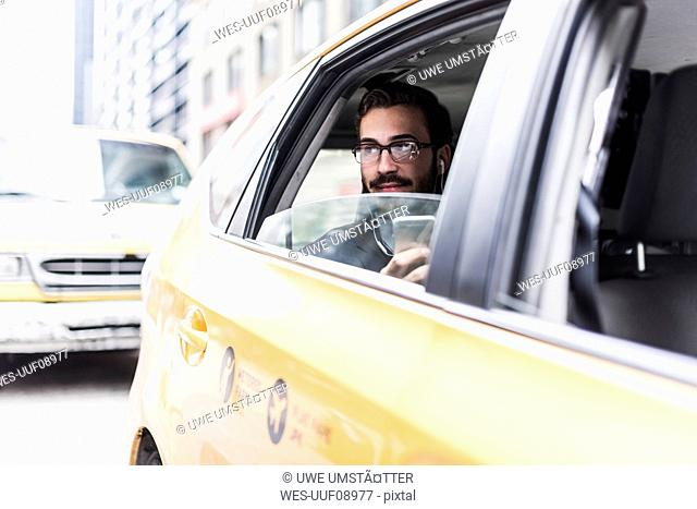 USA, New York City, businessman with cell phone and earphones in a taxi