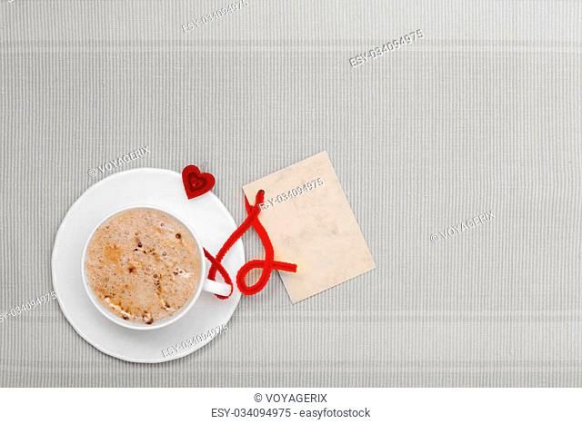White cup of hot beverage drink coffee cappuccino latte with heart shape symbol love and blank paper card space for text message. Valentine's day