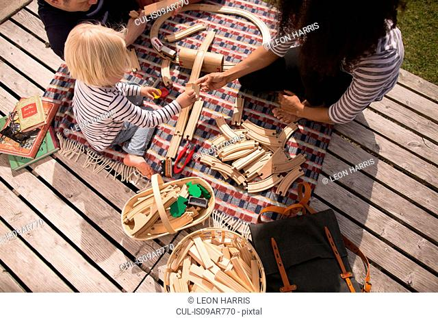 Mother and son playing with wooden toy train track, high angle