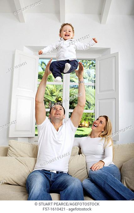 Family on their sofa throwing one year old baby in the air