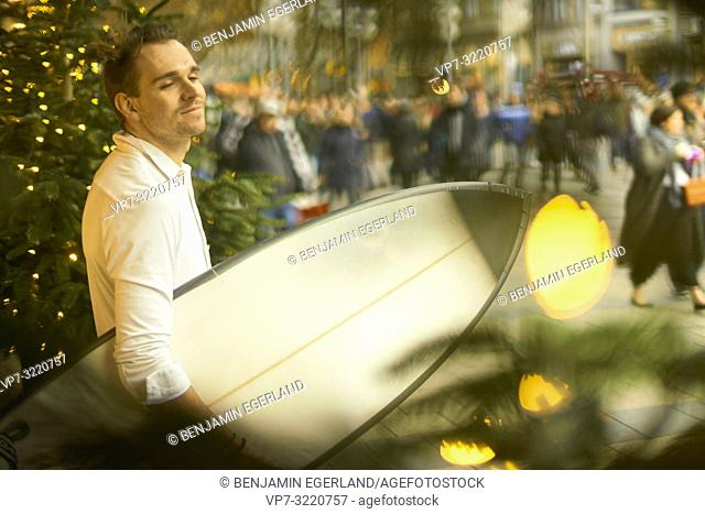 man with surfboard in city, Christmas lights, in Munich, Germany