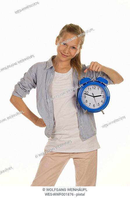 Girl holding alarm clock, smiling, portrait