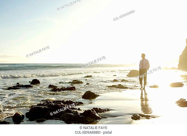 Businessman walking on El Matador beach, California, USA