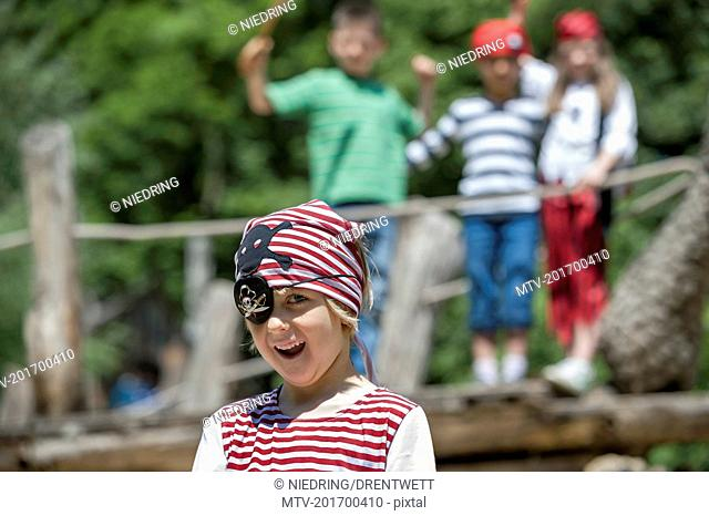Boy dressed up as a pirate playing in adventure playground with his friends in the background, Bavaria, Germany