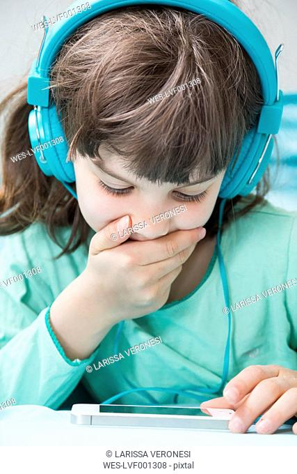 Portrait of little girl with headphones using smartphone