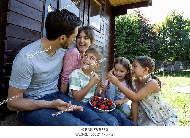 Happy family eating berries at garden shed