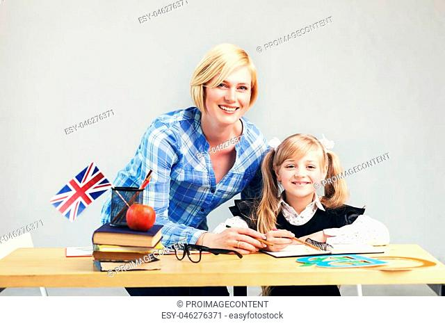 Woman educator helps kid girl to learn English language, school table with books, flag and letters in light classroom