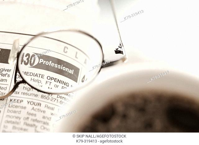 Glasses laying on classified ads with coffee