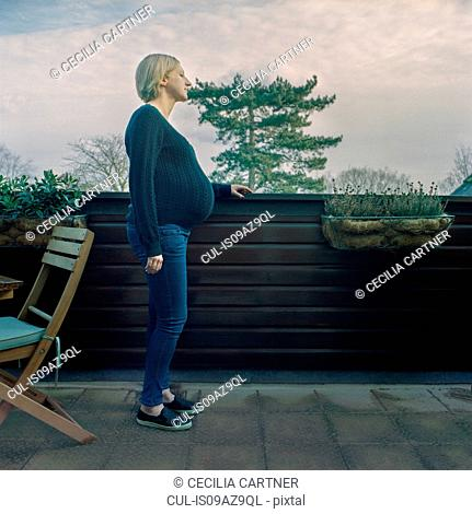 Side view of pregnant woman in garden looking away