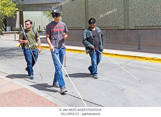 Phoenix, Arizona - Blind and visually impaired young men, some wearing sleep masks, practice navigating city streets with white canes