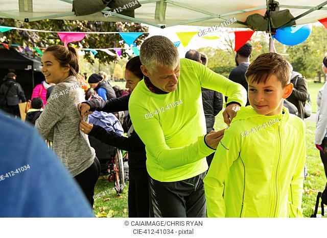 Father pinning marathon bib on son at charity run in park tent
