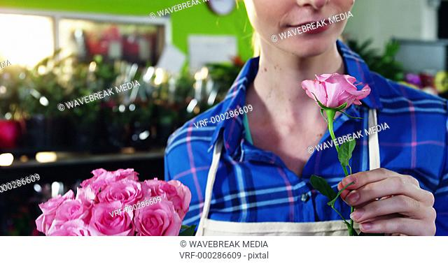 Beautiful female florist smelling bunch of pink rose