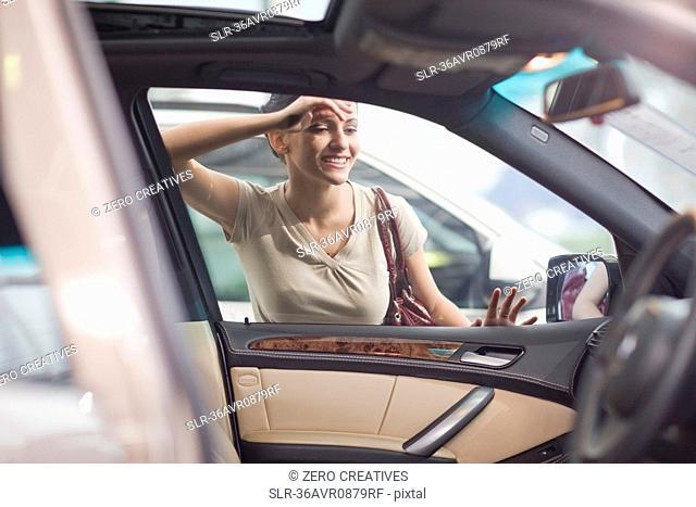 Woman admiring car in showroom