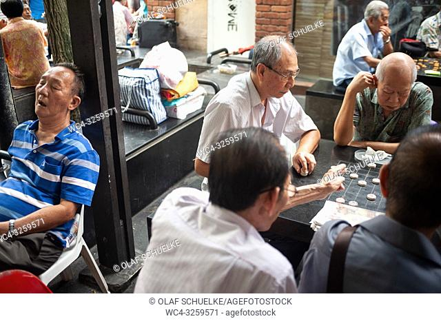 Singapore, Republic of Singapore, Asia - A group of elderly men is seen sitting around the Kreta Ayer Square in Singapore's Chinatown district