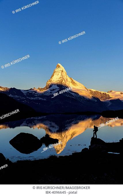 First sunlight on the Matterhorn, with reflection in Stellisee lake, with a person, Zermatt, Canton of Valais, Switzerland