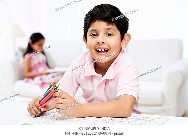 Boy making drawings with his sister in the background