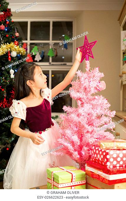 Chinese girl putting a star on her own tree at Christmas