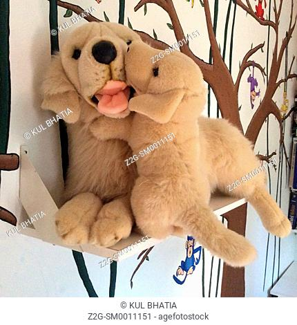 A plush mom and pup cuddle on a shelf in a child's room, Ontario, Canada