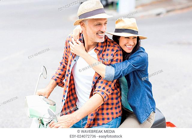 Woman hugging man on moped