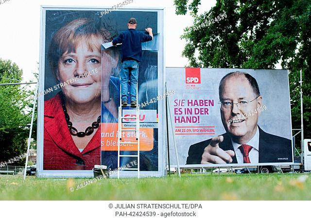 A person places a new election poster for the upcoming federal election of the Christian Democratic Party featuring an image of German Chancellor Angela Merkel...