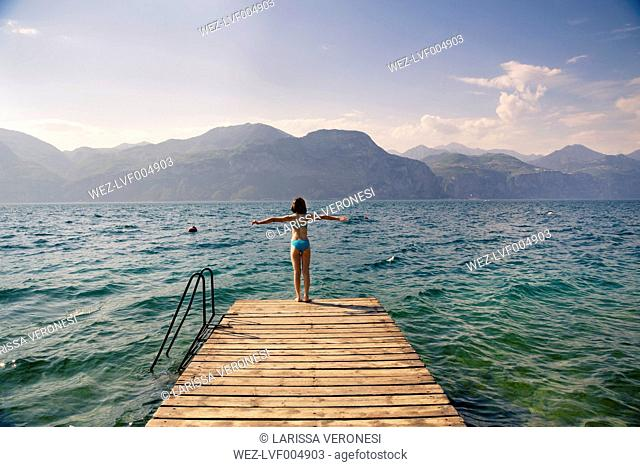 Italy, Brenzone, back view of girl standing on jetty