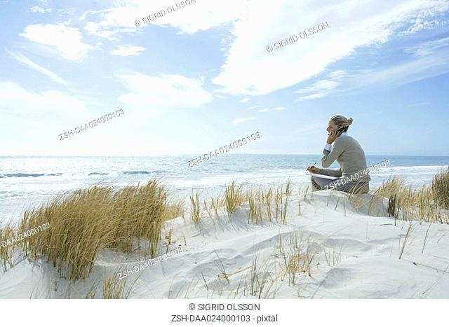 Woman sitting on dunes at beach, using cell phone