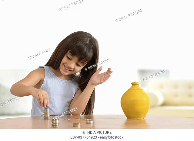 Girl arranging coins on table with clay piggy bank