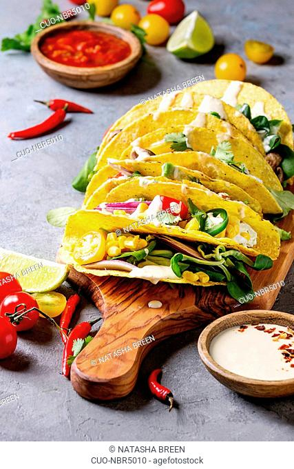 Variety of vegetarian corn tacos with vegetables, green salad, chili pepper served on wooden cutting board with tomato and cream sauces with ingredients above...