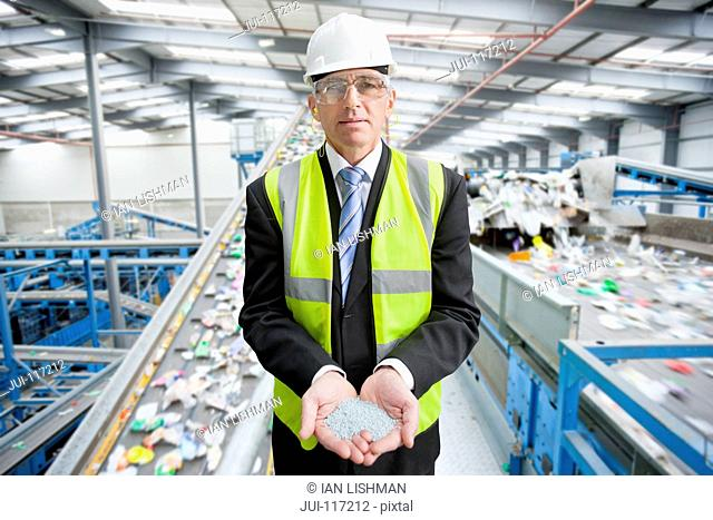 Businessman In Recycling Plant Holding Plastic Pellets
