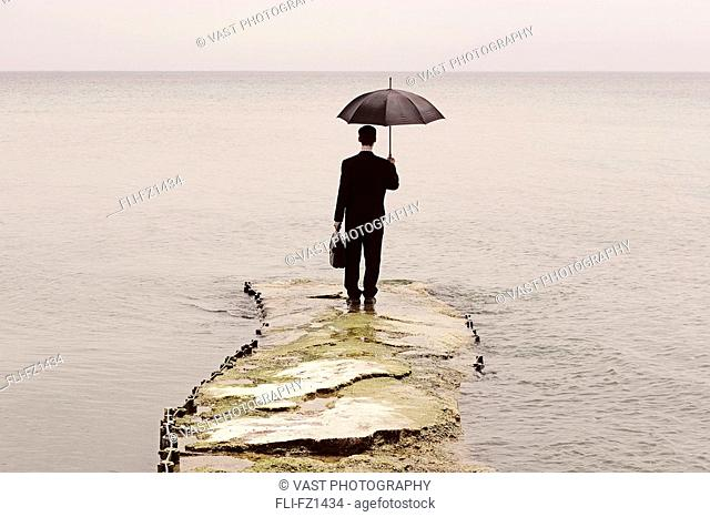 Man in suit holding umbrella and briefcase, standing at end of sinking pier