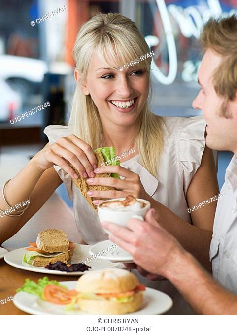 Couple eating sandwiches and drinking lattes at cafe
