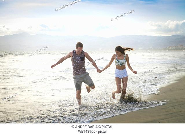 Young man and woman enjoying a run on the beach, Riviera Nayarit, Mexico