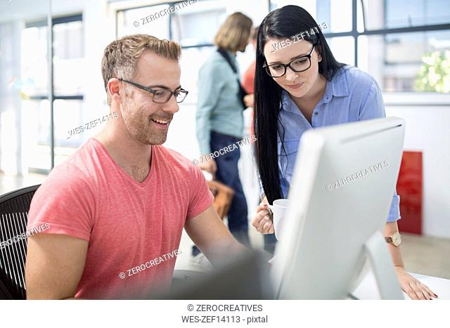 Employees discussing work at their work station