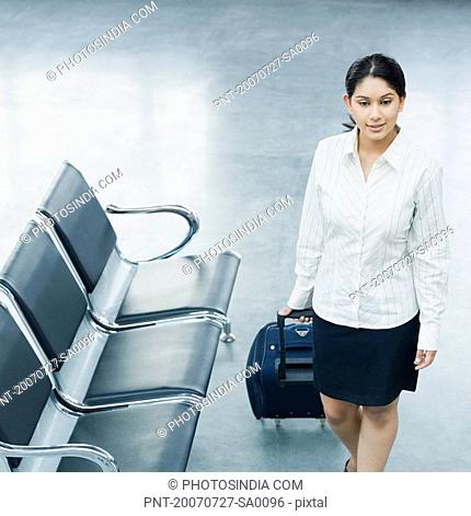 High angle view of a businesswoman pulling her luggage at an airport